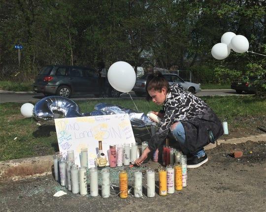 Yamilex Lopez arranges a memorial to victims of a double homicide at Von Nieda Park in Camden Sunday.