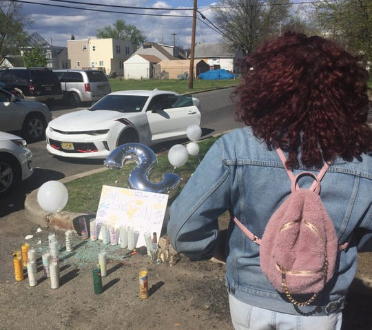 Adrianni Herrera of Camden looks at a memorial to her friend, Shirleen Caban, and two other victims of an early-morning shooting in Cramer Hill Sunday.