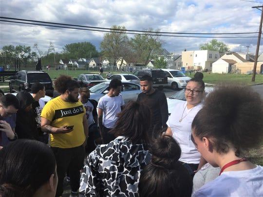 Thalia Cruz, in white shirt, addresses mourners Sunday at scene of Von Nieda Park double homicide.