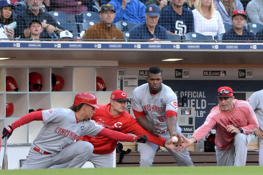 (From left to right) Cincinnati Reds starting pitcher Luis Castillo, manager David Bell, right fielder Yasiel Puig, and hitting coach Turner Ward (31) attempt to catch a foul ball during the second inning against the San Diego Padres at Petco Park.