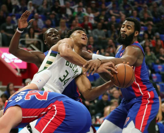 Detroit Pistons center Andre Drummond, left, and guard Reggie Jackson defend Milwaukee Bucks forward Giannis Antetokounmpo in the first quarter of Game 3 of the playoffs Saturday, April 20, 2019 at Little Caesars Arena.