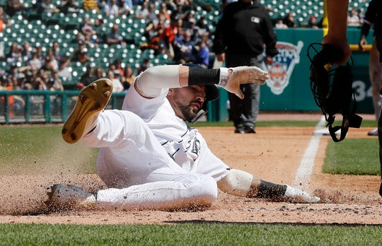 Detroit Tigers' Nicholas Castellanos safely slides to score on a single by teammate Miguel Cabrera during the fourth inning of a baseball game against the Chicago White Sox, Sunday, April 21, 2019, in Detroit.