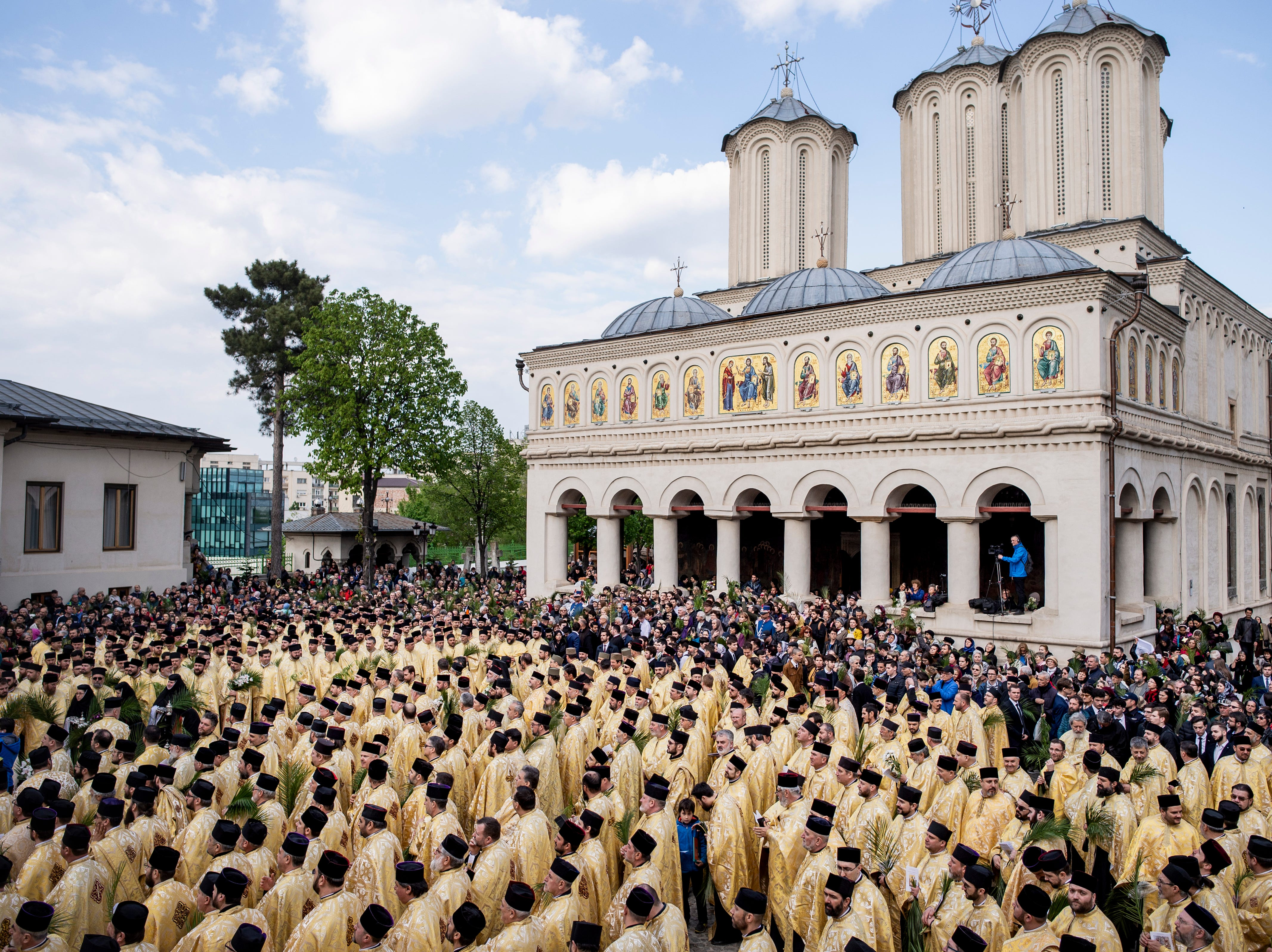 Romanian Orthodox priests and belivers stand outside the Patriarchal Cathedral after an Orthodox Palm Sunday pilgrimage in Bucharest, Romania, Saturday, April 20, 2019. According to local media hundreds of priests and thousands of Orthodox worshippers marched through the Romanian capital and major cities ahead of Palm Sunday.
