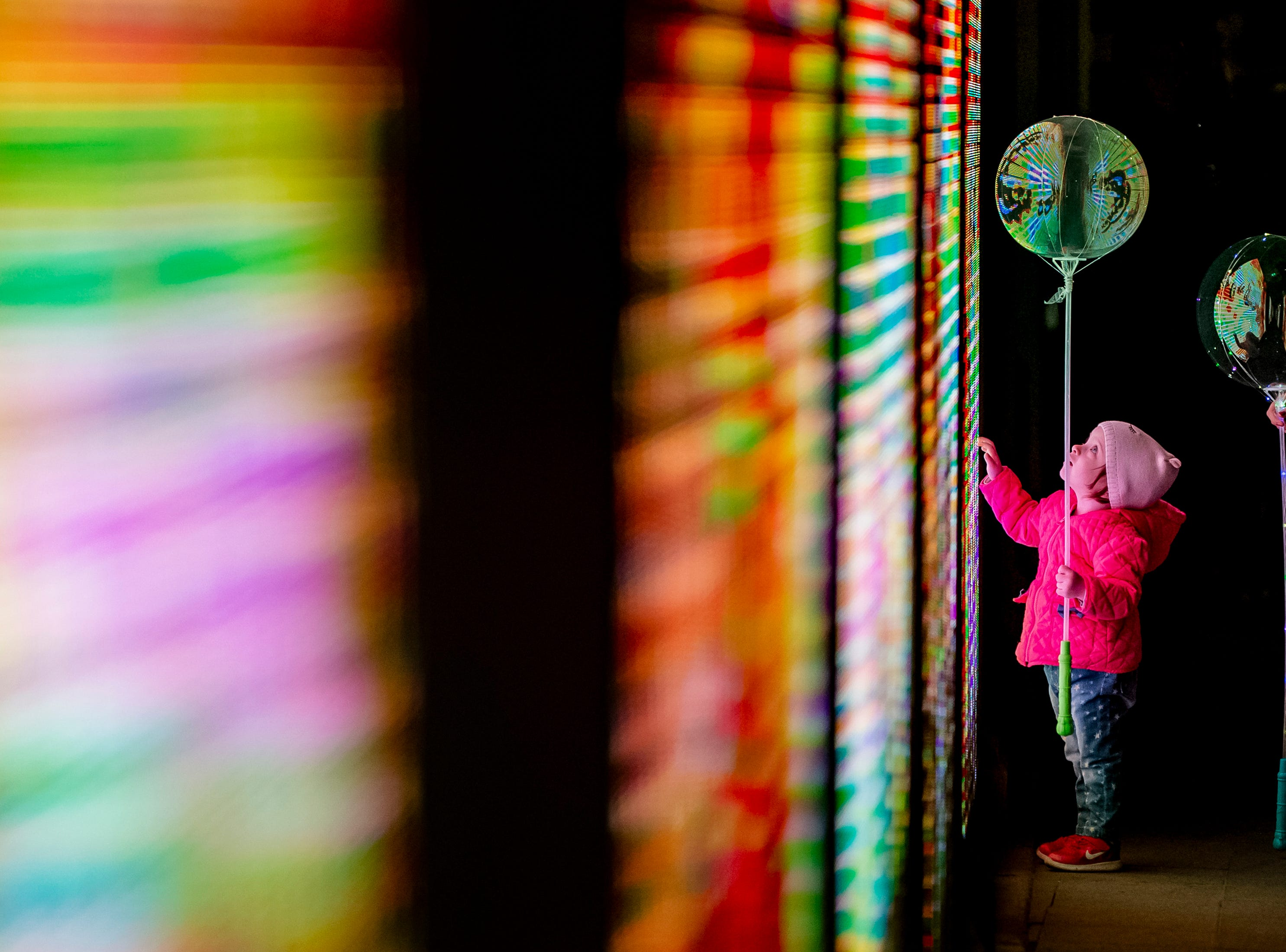 A girl holding a ballon touches an LED panel part of an light installation during Spotlight International Light Show, in Bucharest, Romania, Saturday, April 20, 2019. The international light festival includes light and digital art installations created by local and international artists and runs under the theme EuropeLights marking the Romanian Presidency of the Council of the European Union.