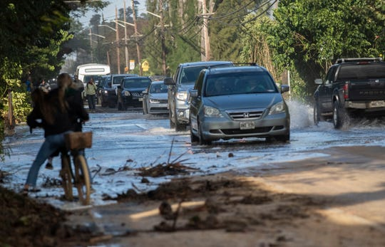 In this Feb. 10, 2019 file photo, vehicles pass through surf that washed over a roadway on Oahu's north shore near Haleiwa, Hawaii.