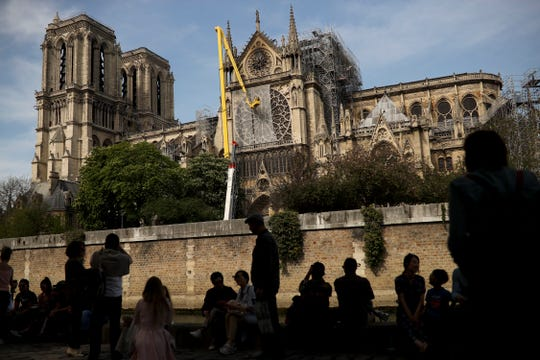 Workers, top, fix a net to cover one of the iconic stained glass windows of the Notre Dame Cathedral in Paris, Sunday, April 21, 2019.