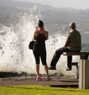 In this Aug. 31, 2015 file photo, T.J. and Misti Madden, of Hilo, Hawaii, watch as a large wave crashes off a sea wall in Hilo, Hawaii as hurricane Ignacio moves past the state.