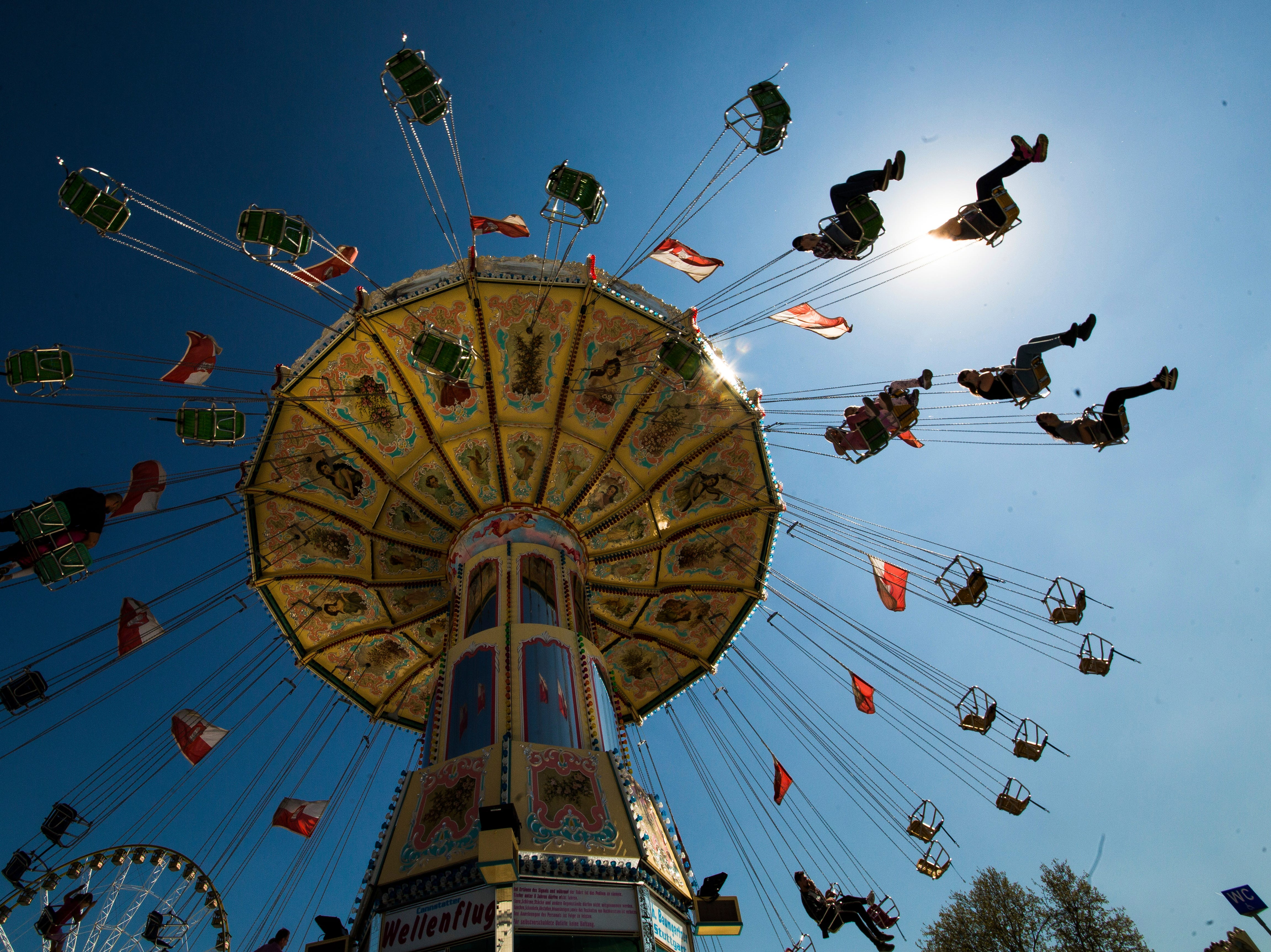 People enjoy a merry-go-round at the traditional spring festival in Stuttgart, Germany, Saturday, April 20, 2019.