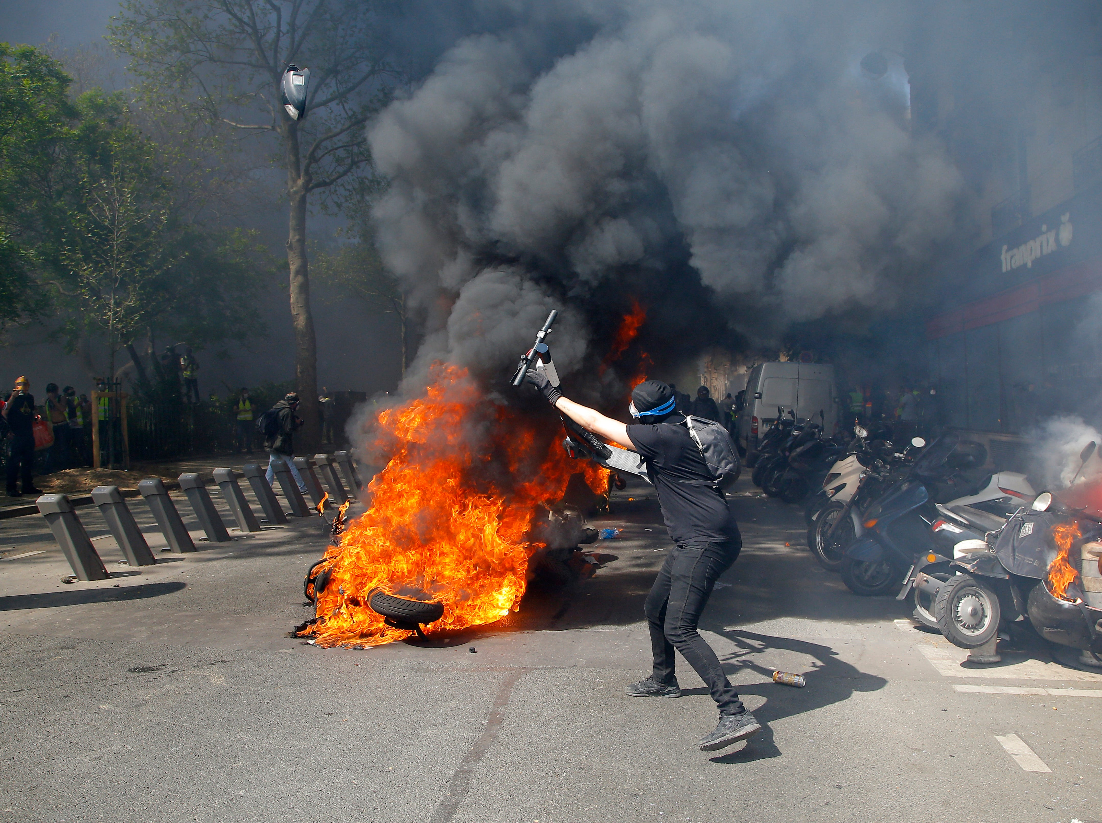 A protestor throws a scooter onto a pile of burning motorbikes during a yellow vest demonstration in Paris, Saturday, April 20, 2019. French yellow vest protesters are marching anew to remind the government that rebuilding the fire-ravaged Notre Dame Cathedral isn't the only problem the nation needs to solve.