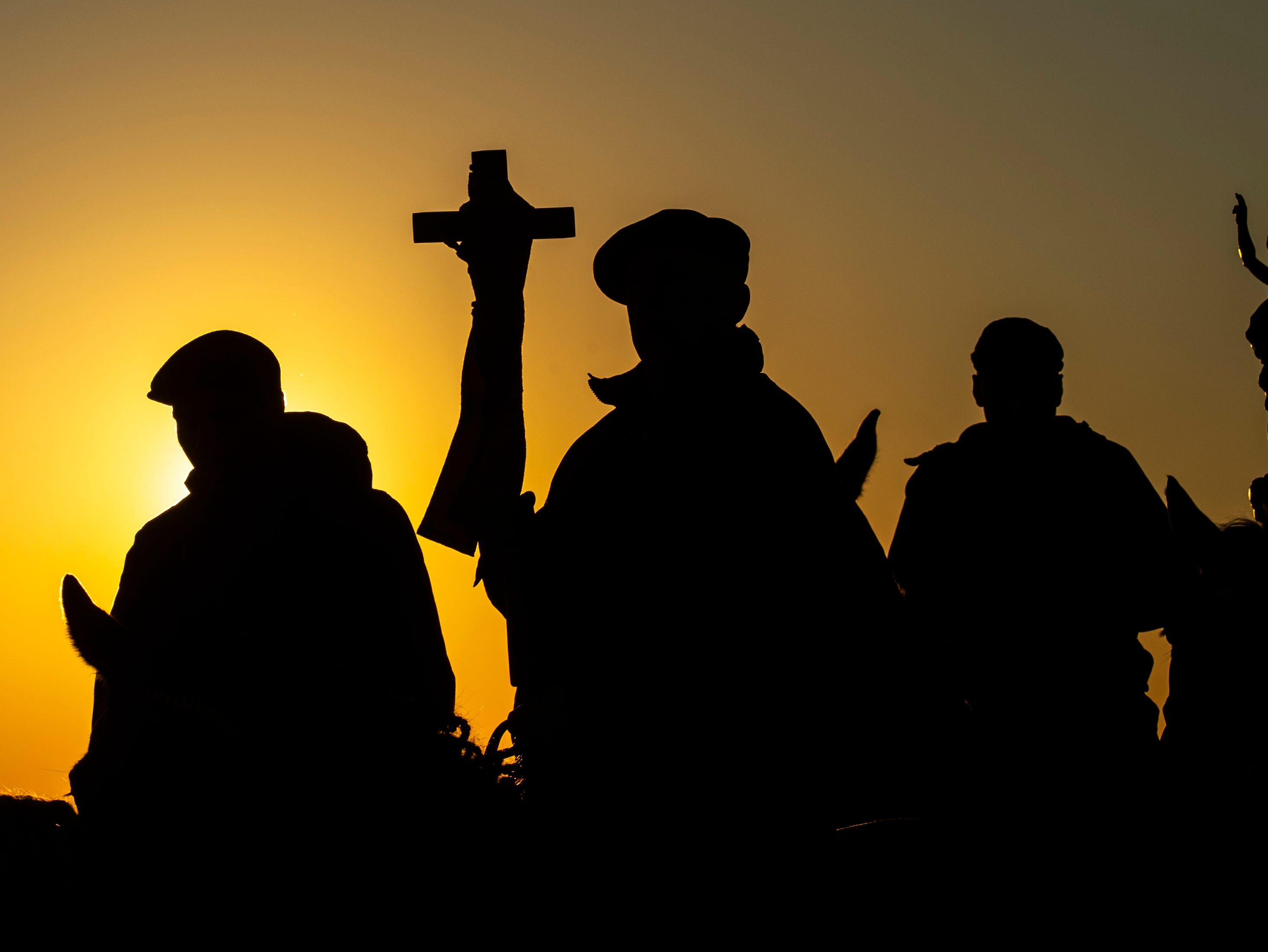 Men carry the cross and a figure at the day's first procession, the so called 'Seed riding' during the sunset at the Easter riders processions in Ostro, eastern Germany, Sunday, April 21, 2019. According to a more than hundred years old tradition men of the Sorbs, dressed in black tailcoats ride on decorated horses, proclaiming, singing and praying the message of Jesus' resurrection. The Sorbs are a Slavic German minority located near the German-Polish border.