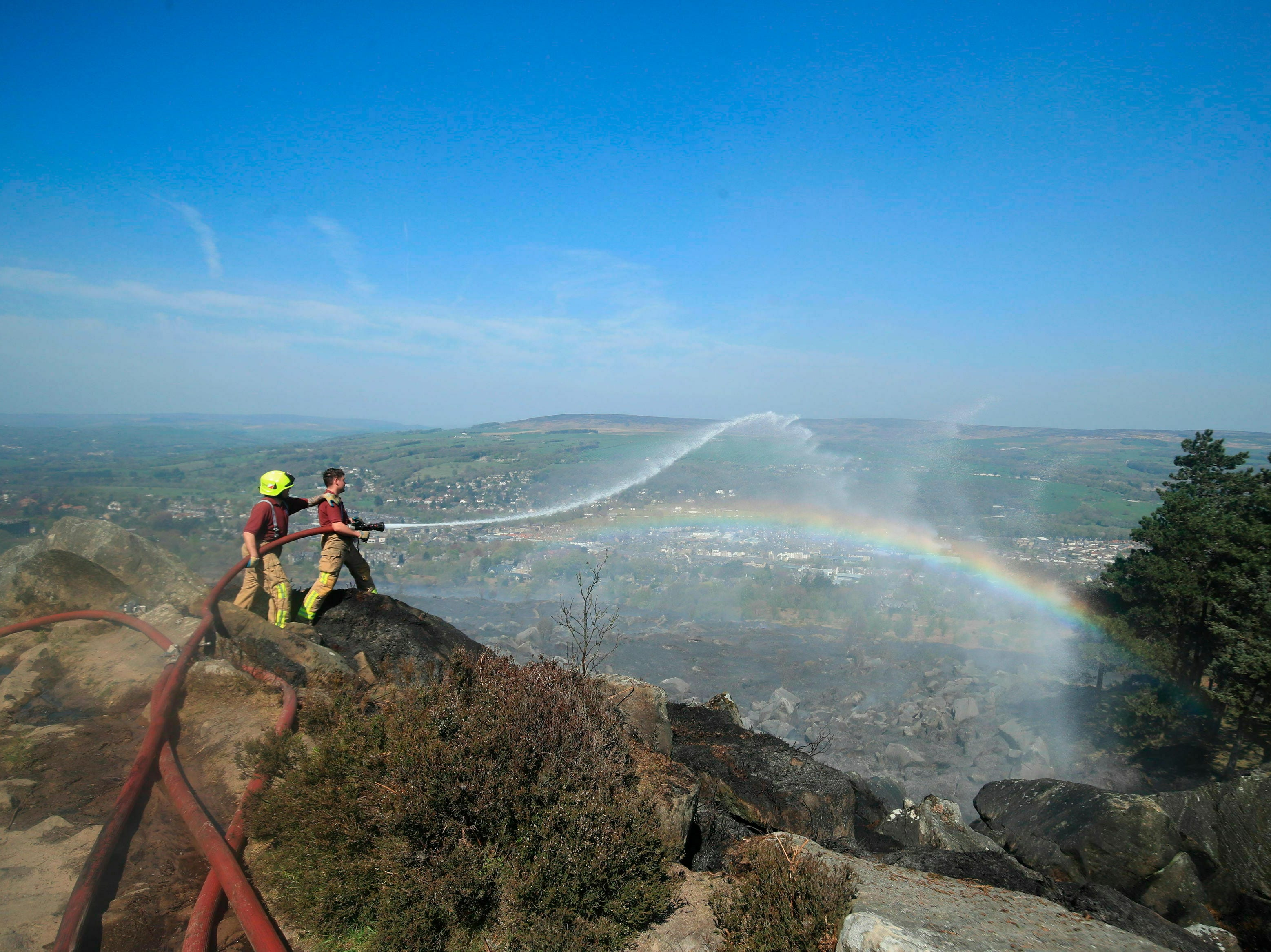 Firefighters tackle a large fire which is continuing to burn on Ilkley Moor in West Yorkshire, north England, Sunday April 21,