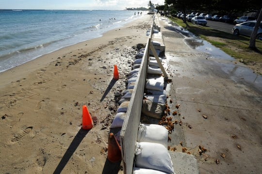 In this June 23, 2017 photo, sand bags line the beach at Ala Moana Beach Park in Honolulu as record high tides hit the islands.