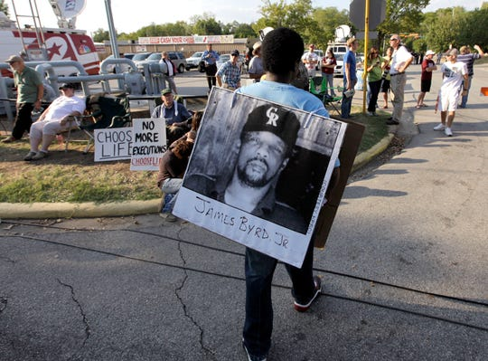 In this Sept. 21, 2011, file photo, Ricky Jason wears a photograph of James Byrd Jr. outside the Texas Department of Criminal Justice Huntsville Unit before the execution of Lawrence Russell Brewer in Huntsville, Texas.