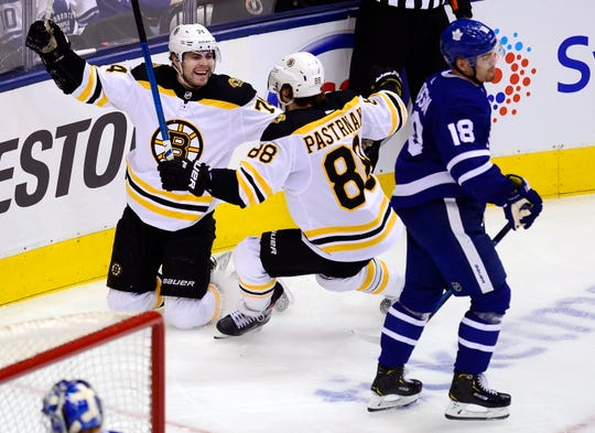 Bruins left wing Jake DeBrusk (74) celebrates his goal with right wing David Pastrnak (88) as Maple Leafs left wing Andreas Johnsson (18) skates by during the second period of Game 6 on Sunday.