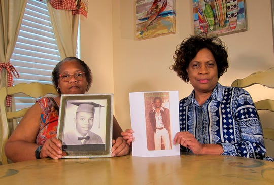 Mylinda Byrd Washington, 66, right, and Louvon Byrd Harris, 61, hold up photographs of their brother James Byrd Jr. in Houston.