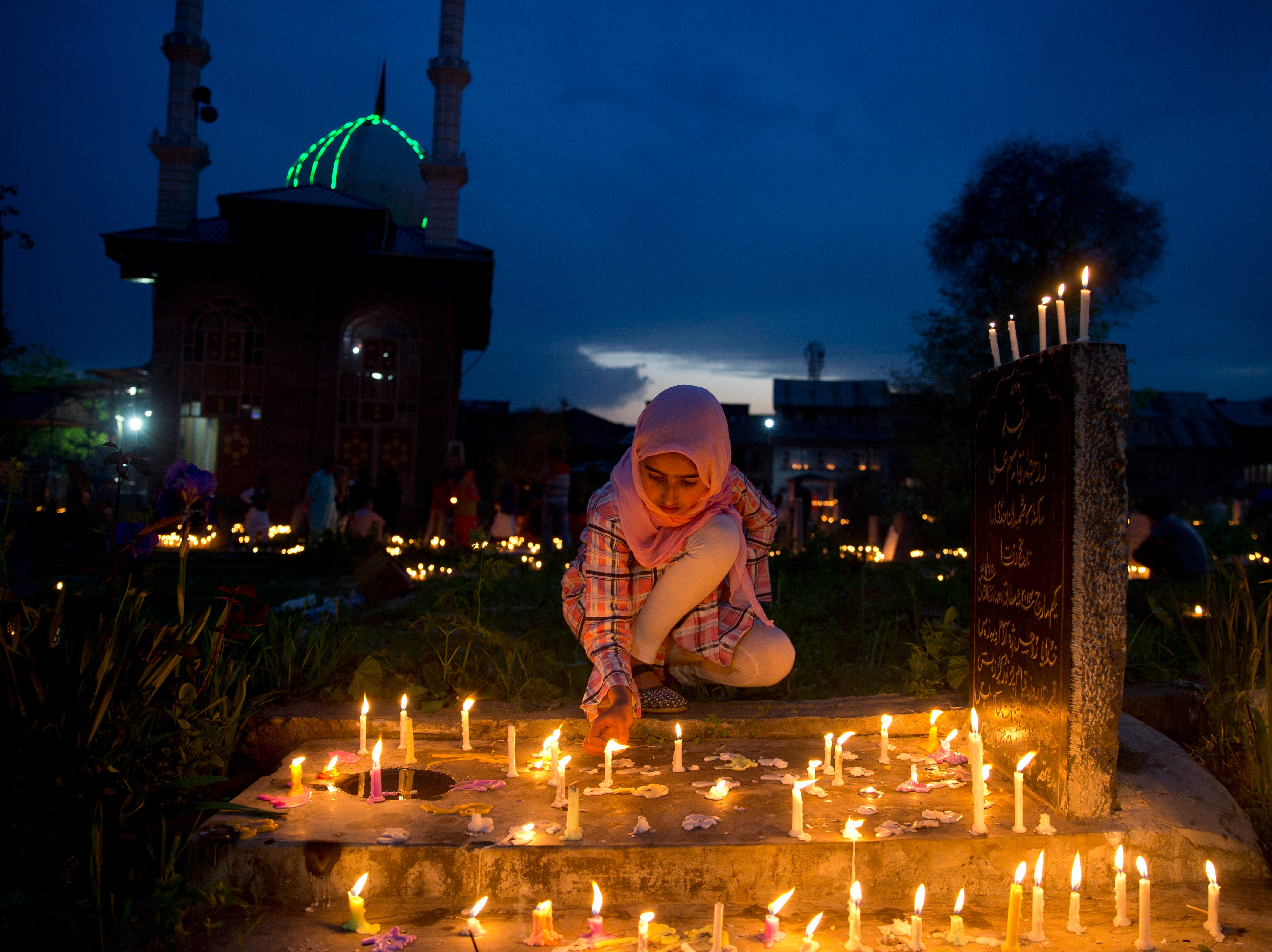 A Kashmiri Shiite Muslim girl light candles on the grave of her relative to mark Shab-e-Barat, on the outskirts of Srinagar, Indian controlled Kashmir, Saturday, April 20, 2019. Muslims visit ancestral graveyards for the salvation of the souls of the departed and also believe that all sins will be forgiven by praying to Allah throughout the Shab-e Barat night.
