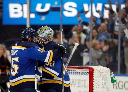 St. Louis Blues' Robby Fabbri, left, and goaltender Jordan Binnington celebrate after defeating the Winnipeg Jets in Game 6 to win the series.