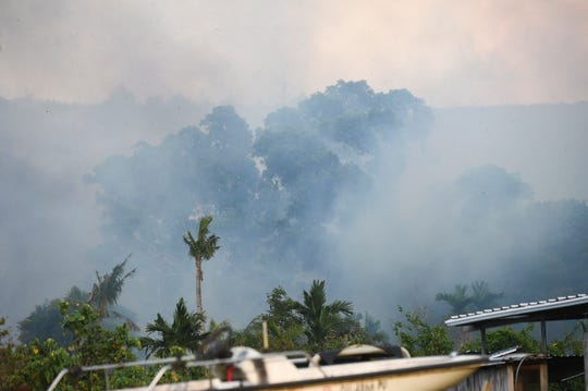 Smoke from a grass fire fills the surrounding area of Chalan Kindo Street and Chalan Lizama Street in Santa Rita, April 21, 2019.