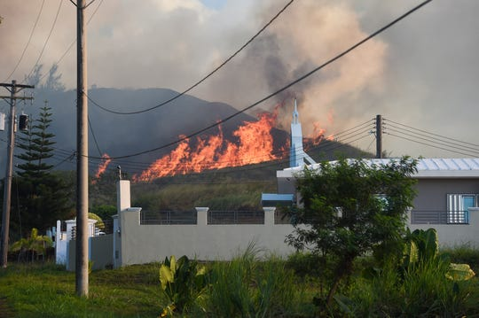 A grass fire blazes on a hill behind Iglesia ni Christo in Santa Rita on April 21, 2019.