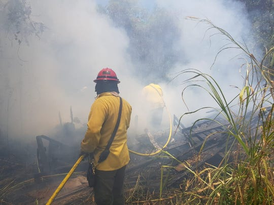 The Guam Fire Department battles a grass fire in Barrigada, behind Katz and Sons, on Sunday afternoon.