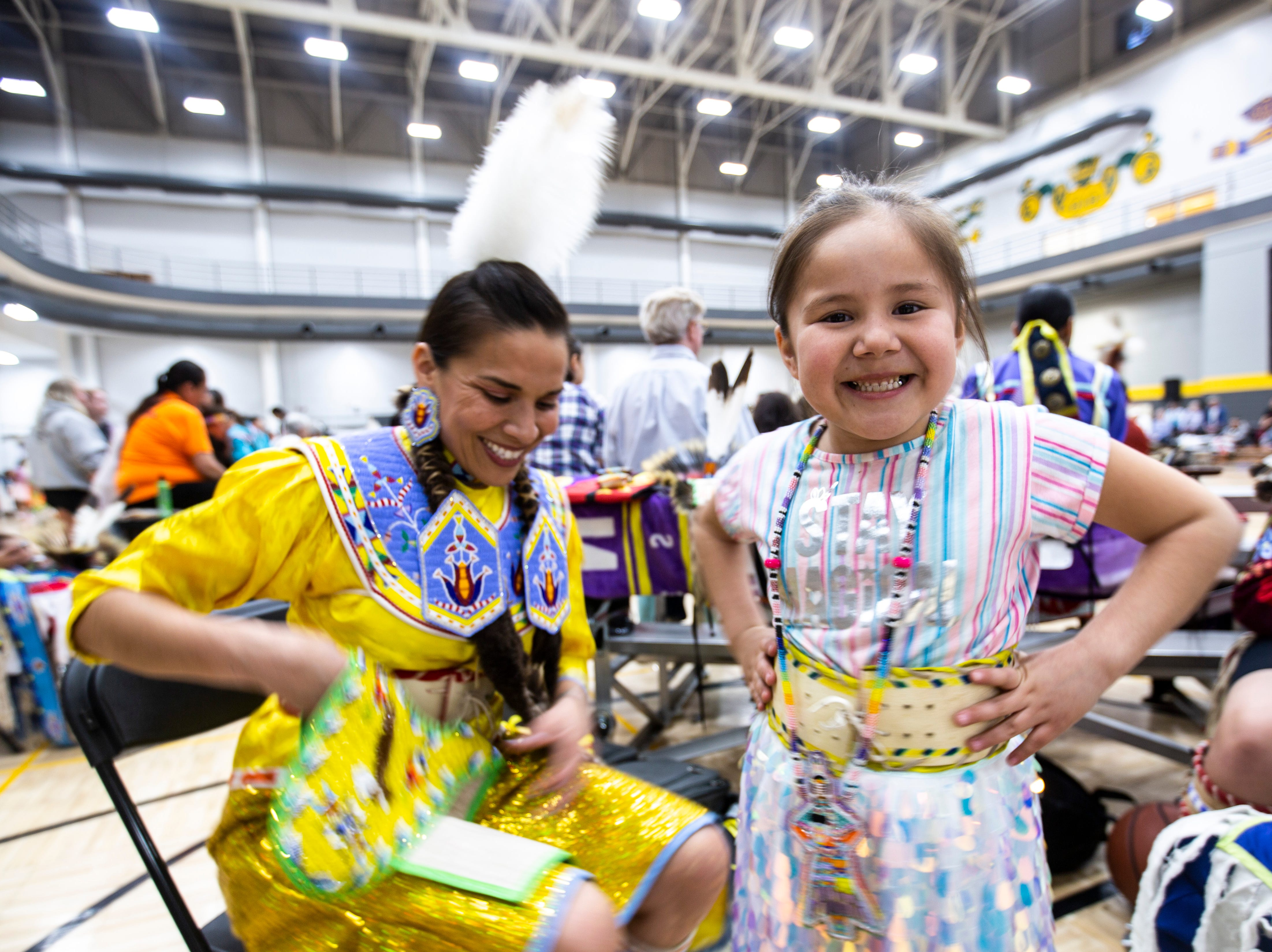 Tess Lasley, 6, smiles before while her mother, Nahmi, of the Comanche and Dakota tribes in Tama, Iowa, helps her get ready before a dance during the 25th annual University of Iowa powwow, Saturday, April 20, 2019, at the Field House on the University of Iowa campus in Iowa City, Iowa. The family has been attending the powwow every year since is first began.