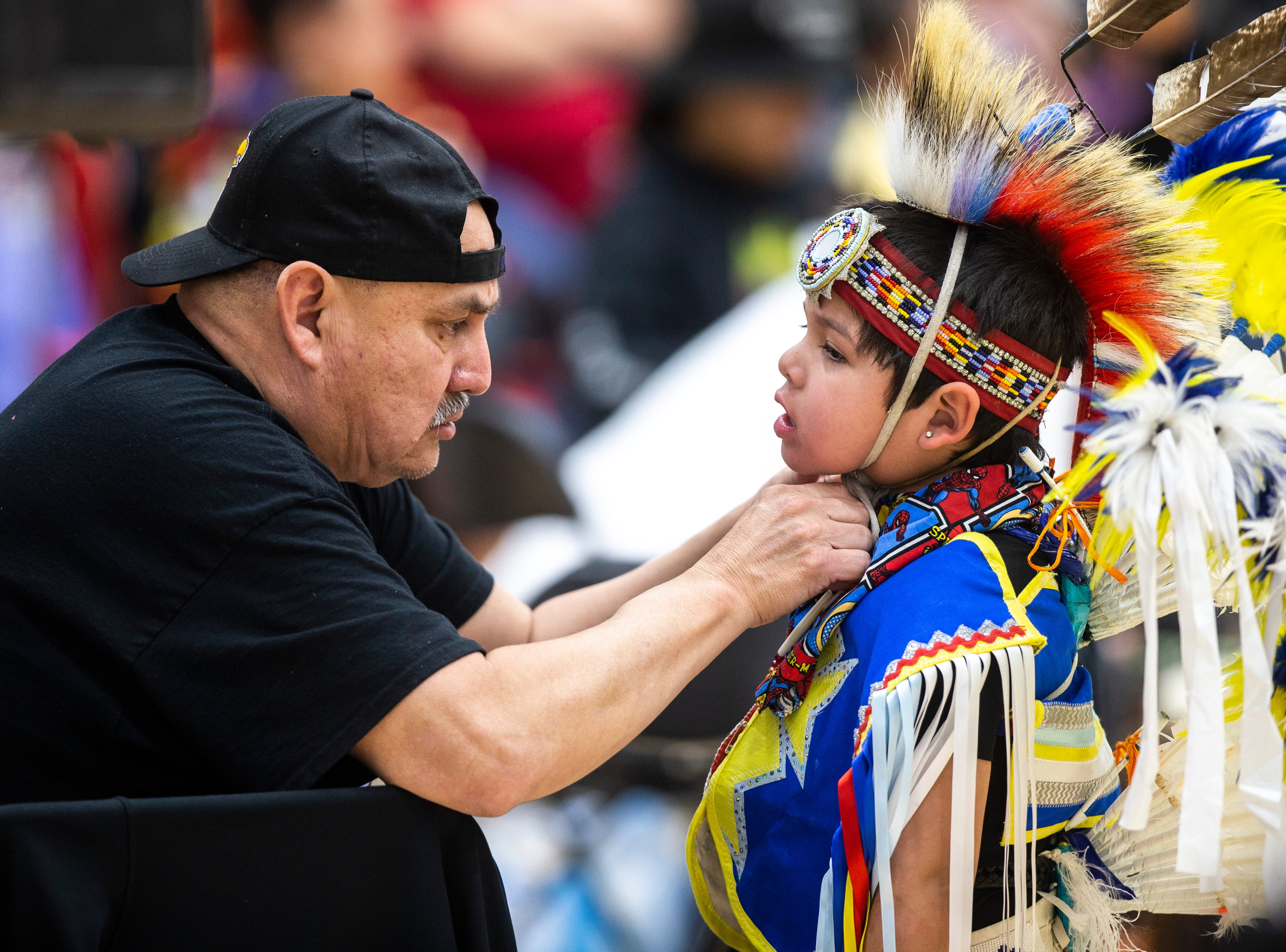 Marshal Demarce, of the Meskwaki Indian settlement in Tama, Iowa, helps his grandson Leriss Keanna, 4, before dancing during the 25th annual University of Iowa powwow, Saturday, April 20, 2019, at the Field House on the University of Iowa campus in Iowa City, Iowa. Drums from White Tail, Nebraska, Eagle Feather, Iowa and the Meskwaki Nation, Iowa participated in the event.