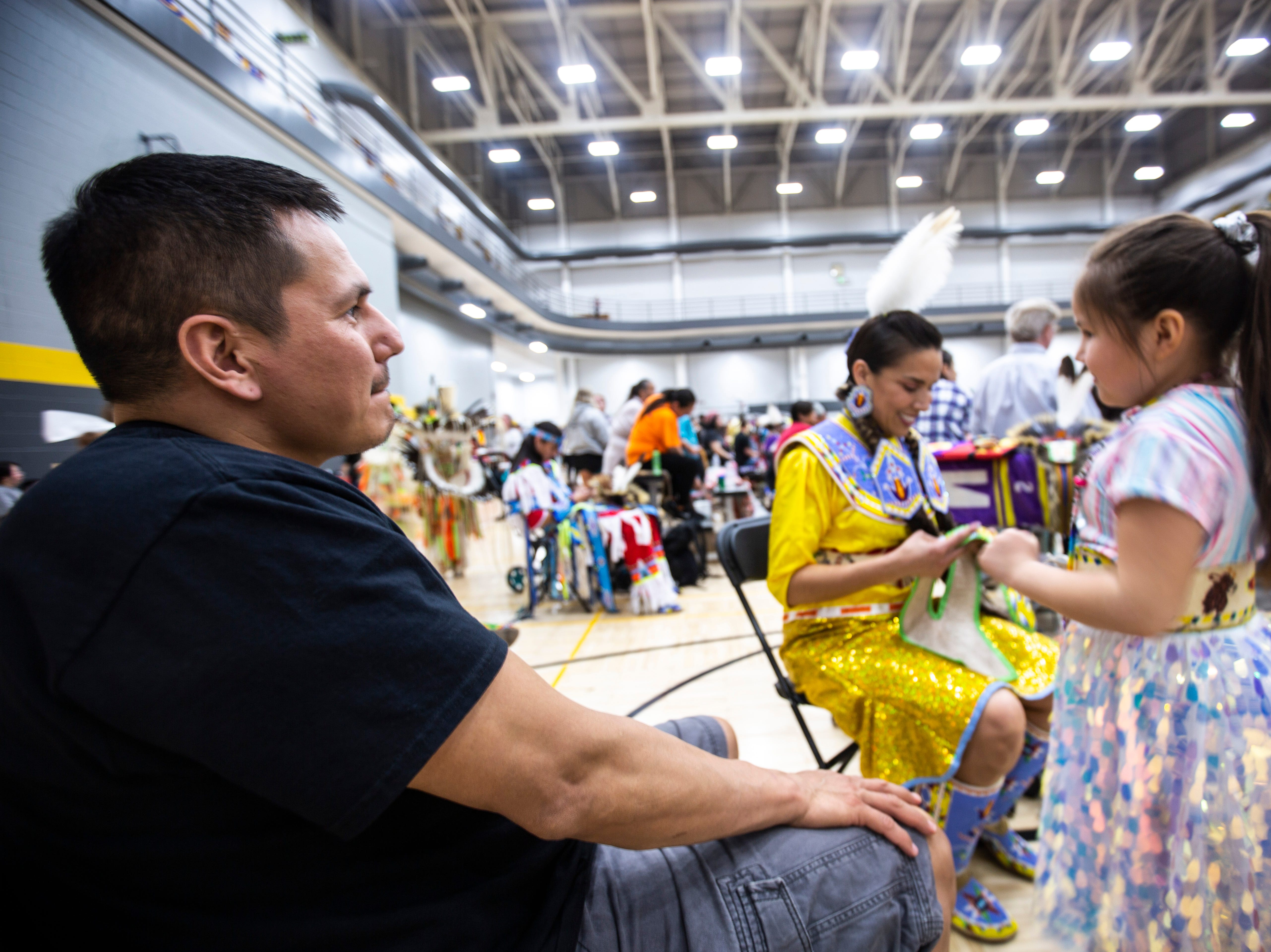 Tyler Lasley, of Tama, Iowa, watches as his wife Nahmi helps their daughter Tess, 6, get ready before a dance during the 25th annual University of Iowa powwow, Saturday, April 20, 2019, at the Field House on the University of Iowa campus in Iowa City, Iowa. The family has been attending the powwow every year since is first began.