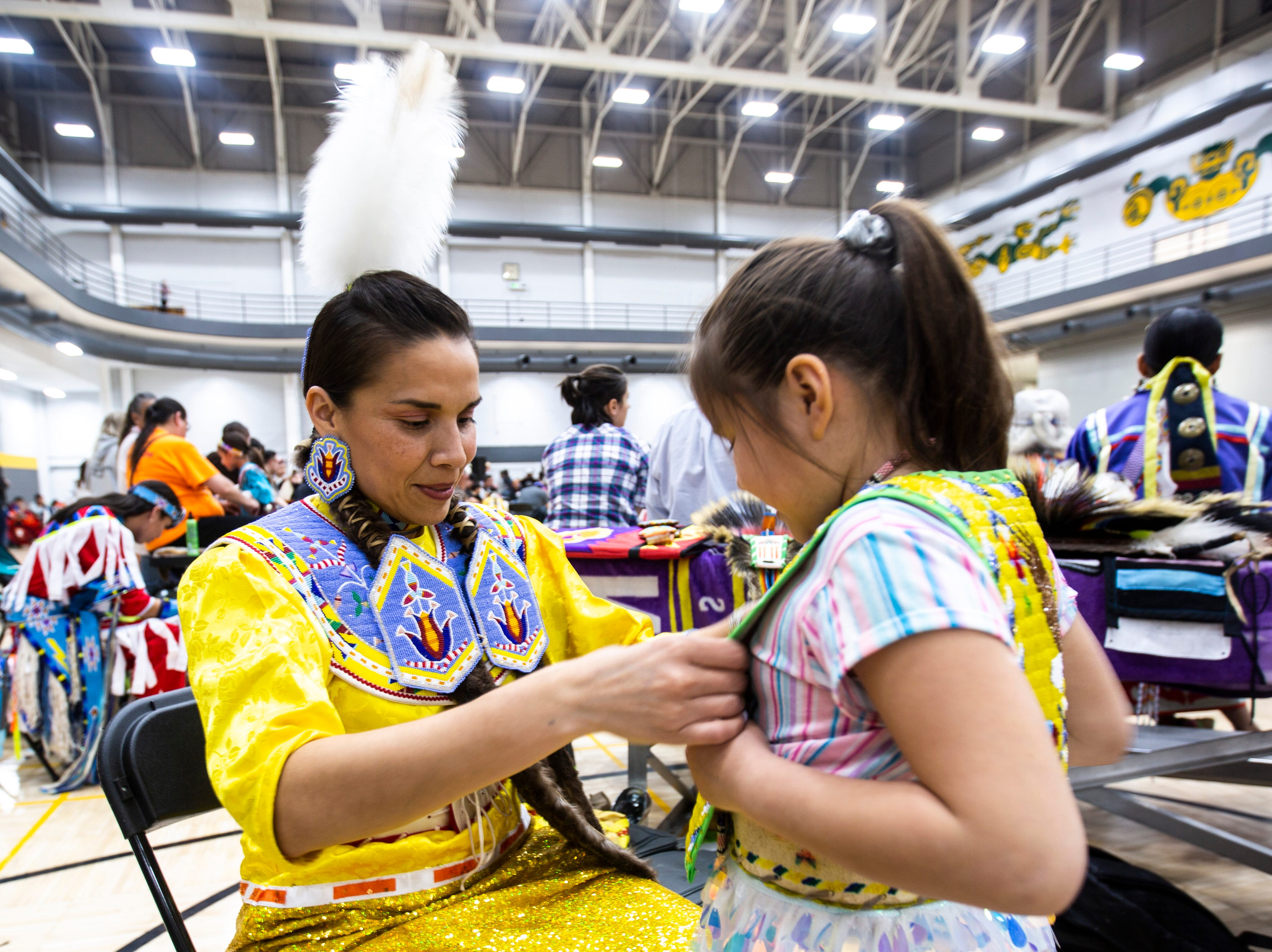 Nahmi Lasley helps her daughter Tess, 6, get ready before a dance during the 25th annual University of Iowa powwow, Saturday, April 20, 2019, at the Field House on the University of Iowa campus in Iowa City, Iowa. The family has been attending the powwow every year since is first began.