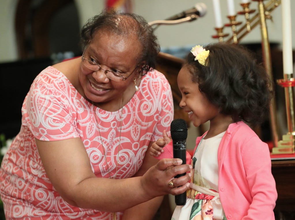 Darlene Harper holds the microphone for Trinity Crouther, 10, as she and other children told the Easter story in poems and readings.
