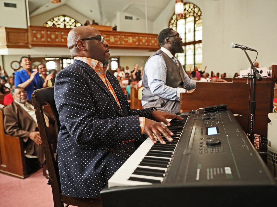 Darren Buckley, left, on keyboard, and Bruce Furlow, playing the organ, have the congregation on its feet during a fast-paced up-tempo song.