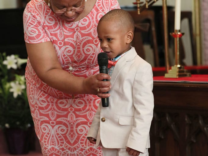 Darlene Harper holds the microphone for Jordan Roberts, 3, as he and other children told the Easter story in poems and readings.