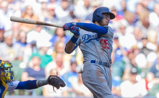 Cody Bellinger hits an RBI single during the second inning against the Brewers on Sunday.