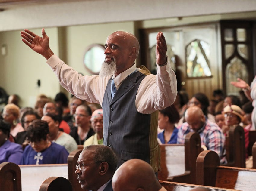 Gregory Roberts stands with his hands raised in praise during Covenant Missionary Baptist Church's Easter service Sunday. The Milwaukee church is celebrating its 40th anniversary this year.