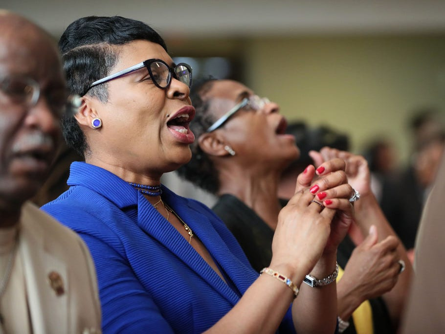 Penny McGee, left, and Grenada McDonald sing during the service.