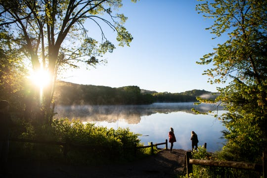 Members of Southminster Presbyterian Church stand before Radnor Lake after the Easter Sunday sunrise service at Radnor Lake State Park Sunday, April 21, 2019, in Nashville, Tenn.