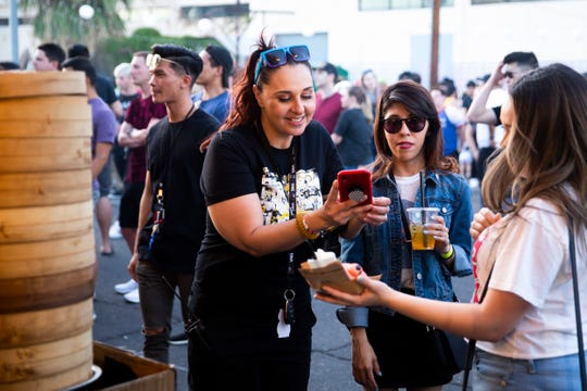 Zee Paralta (left) takes photos of food at the Phoenix Night Market on April 20, 2019. The Phoenix Night Market was open from 5 p.m. until midnight.
