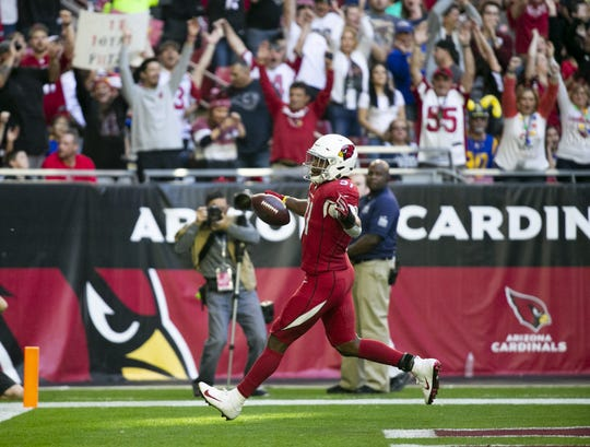 Cardinals running back David Johnson scores a touchdown after catching a pass from Larry Fitzgerald during the second quarter of the NFL game against the Rams at State Farm Stadium in Glendale on Sunday, December 23, 2018.