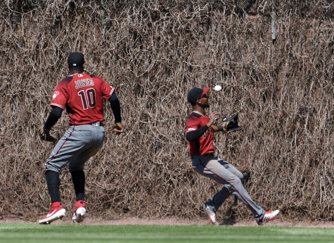 Apr 21, 2019; Chicago, IL, USA; Arizona Diamondbacks center fielder Jarrod Dyson (right) can't catch Chicago Cubs shortstop Javier Baez (not pictured) one run triple during the sixth inning at Wrigley Field.