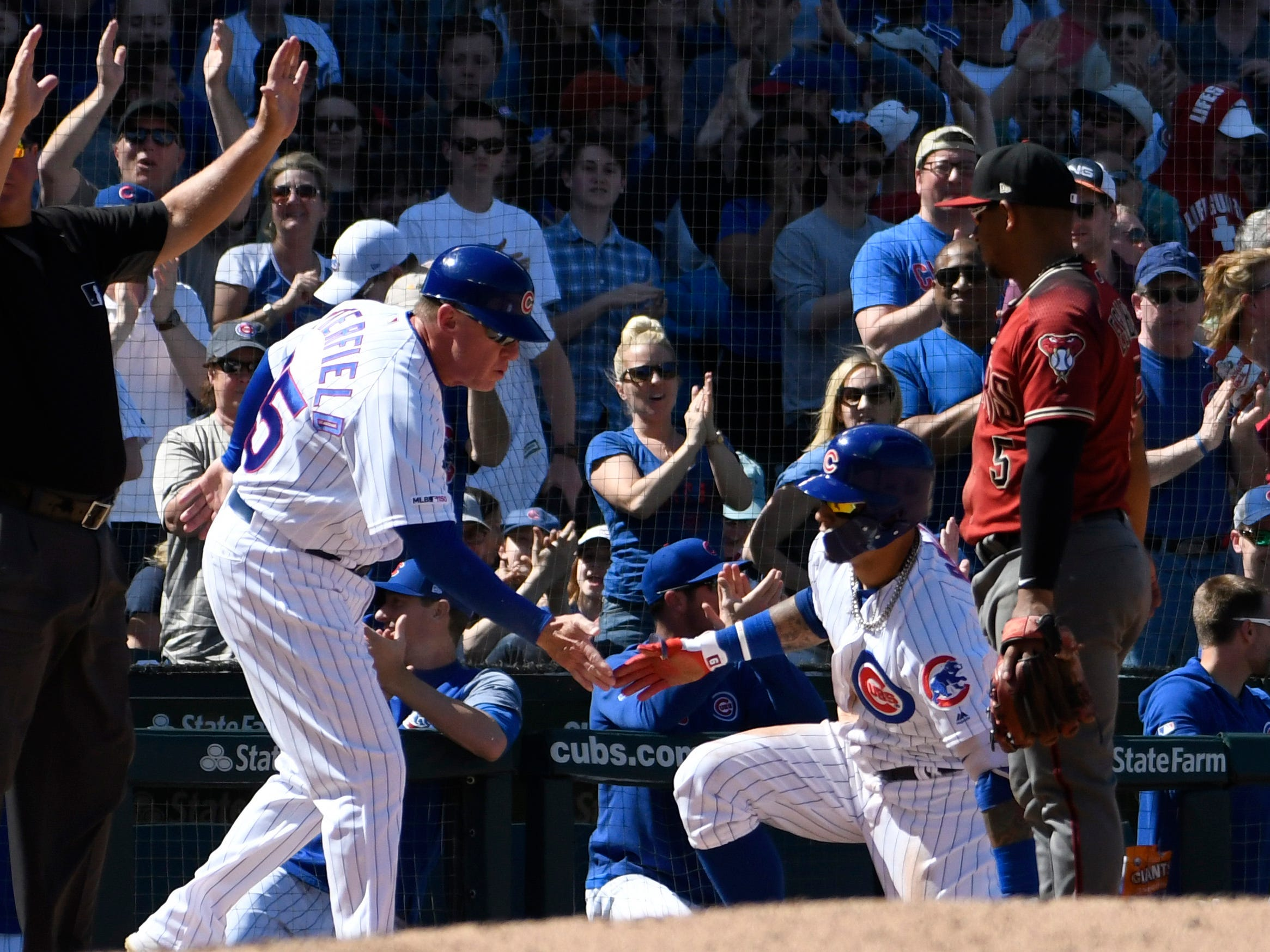 Apr 21, 2019; Chicago, IL, USA; Chicago Cubs shortstop Javier Baez (right) is greeted at third base by third base coach Brian Butterfield (55) after hitting a one run triple against the Arizona Diamondbacks at Wrigley Field.