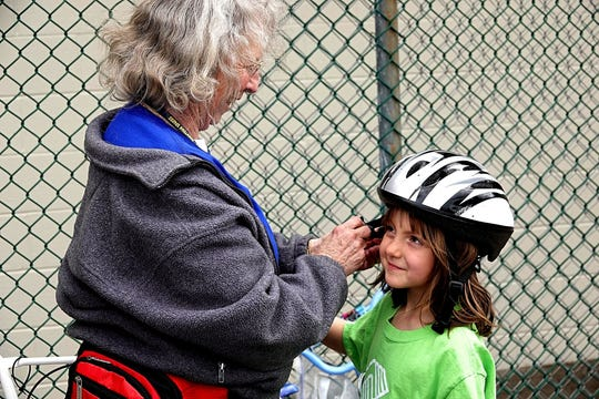 A volunteer secures a helmet on a girl during the first annual Optimist Club of Reno Bike Rodeo on Saturday, April 20, 2019.