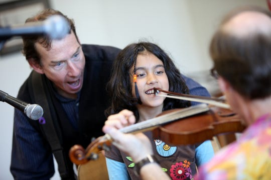 From 2010: John Dady watches as Meena Potter of Pittsford helps Joe Dady play the fiddle while The Dady Brothers perform at the Pittsford Community Library.