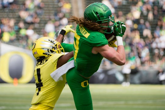 Apr 20, 2019; Eugene, OR, USA; Oregon Ducks wide receiver Brenden Schooler (9) catches a pass for a first down against cornerback Thomas Graham Jr. (4) during the Oregon spring game at Autzen Stadium. Mighty Oregon beat Fighting Ducks 20-13. Mandatory Credit: Troy Wayrynen-USA TODAY Sports