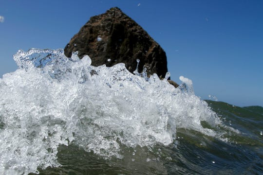 Haystack Rock looms in the background as waves crash ashore in Cannon Beach, Ore., Aug. 26, 2010.