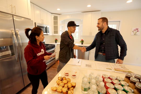 Valon Nikci, broker/owner of Link NY Realty in Bronxville, right, greets prospective home buyers Kelvin Duen and Sharon Estaris during an open house in White Plains April 21, 2019. Nikci says that the real estate market in Westchester County remains strong, especially for homes priced under $800,000.