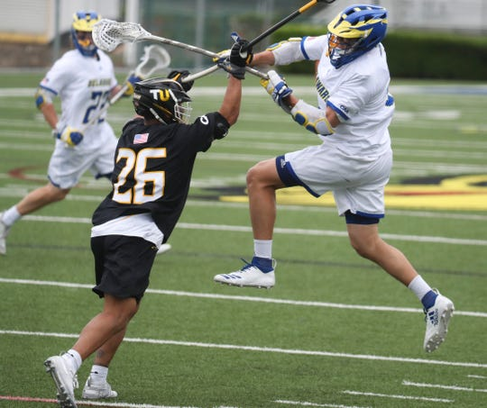 Delaware's Charlie Kitchen (right) shoots and scores over Towson's Koby Smith in the Blue Hens' 14-12 loss at Delaware Stadium on April 20.