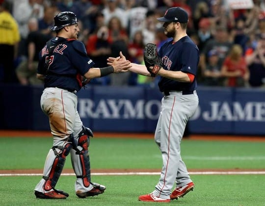 Boston Red Sox relief pitcher Ryan Brasier, right, and catcher Christian Vazquez celebrate after closing out the