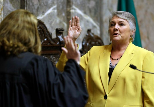 In this Jan. 9, 2017 file photo, Sen. Maureen Walsh, R-Walla Walla, right, takes the oath of office on the opening day of the 2017 legislative session at the Capitol in Olympia, Wash. Sen. Walsh has angered nurses by commenting in a speech that some nurses may spend a lot of time playing cards in rural hospitals.