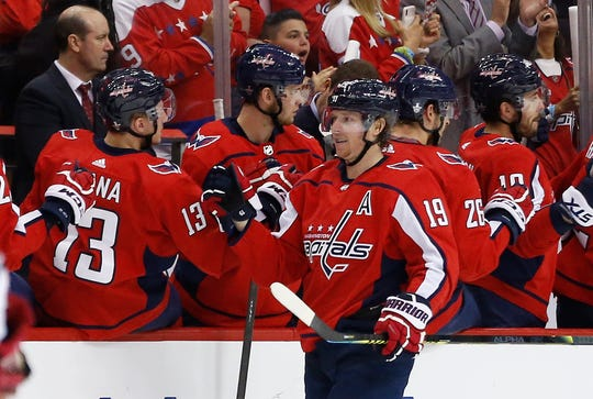 Nicklas Backstrom celebrates with teammates after scoring a goal against the Carolina Hurricanes.