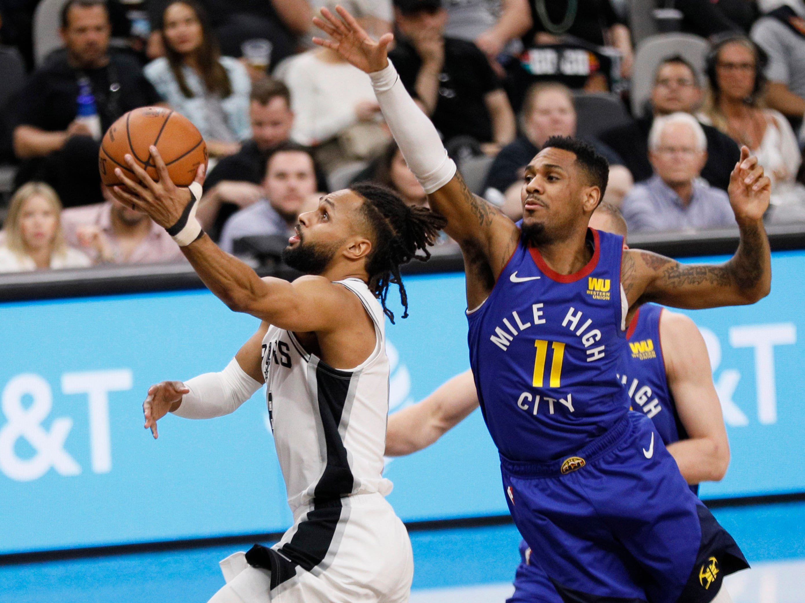 April 20: Spurs guard Patty Mills (8) moves to the basket past Nuggets defender Monte Morris (11) during Game 4.