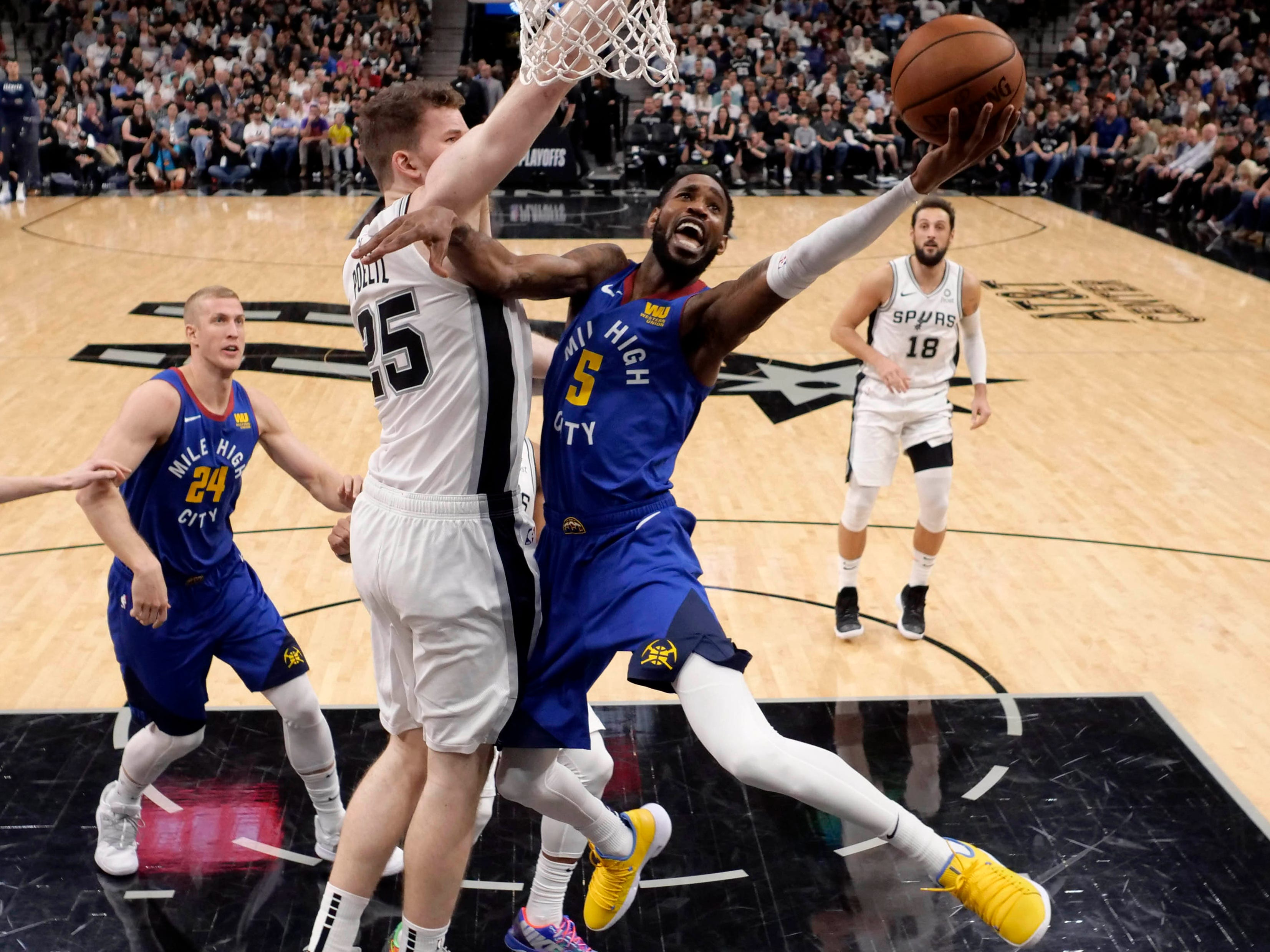 April 20: Nuggets guard Will Barton (5) drives to the bucket against Spurs defender Jakob Poeltl (25) during Game 4 in San Antonio.